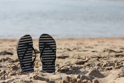 Summer flip flops in the sand. Holiday feeling.