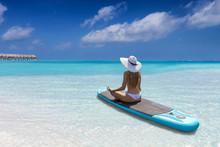 Attraktive Frau In Weißem Bikini Entspannt Auf Einen Surfbrett (SUP) Am Strand Der Malediven