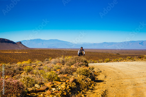 Tuinposter Honing A man rides his bicycle on a dirt road in the mountains of the Karoo, South Africa
