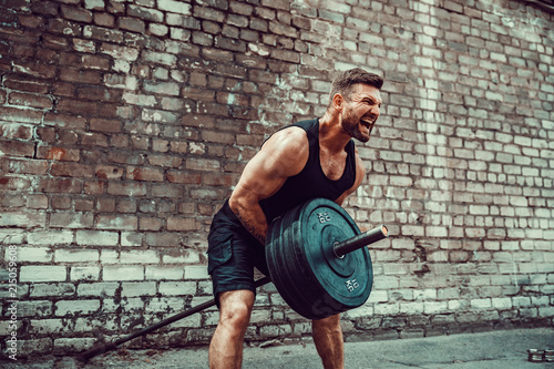 Fotografía  Athletic man working out with a barbell in front of brick wall