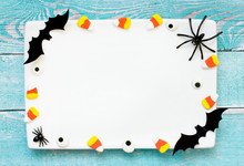 Halloween Background White Empty Plate Decorated With Halloween Symbols Sweet Candy Corn, Bat, Spider, Candy Eyeball