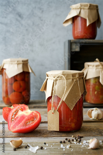 Photo  Autumn preserves of tomatoes and vegetable puree in glass jars placed in wooden box