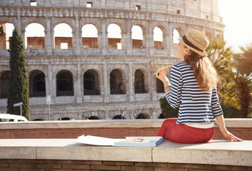 Fototapeta young woman in front of Colosseum in Rome, Italy eating pizza