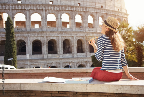 Fényképezés  young woman in front of Colosseum in Rome, Italy eating pizza
