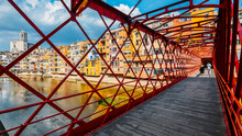 Colorful Houses Seen Through The Red Iron Bridge In Girona, Catalonia, Spain