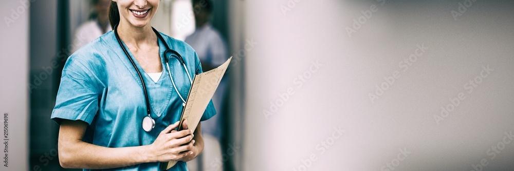 Fotografie, Obraz Portrait of nurse smiling while holding file