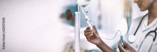 Fotografiet  Nurse connecting an intravenous drip