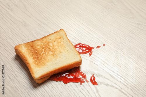 Overturned toast bread with jam on floor