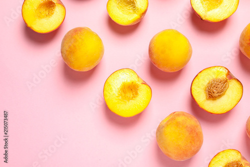 Flat lay composition with ripe peaches on color background