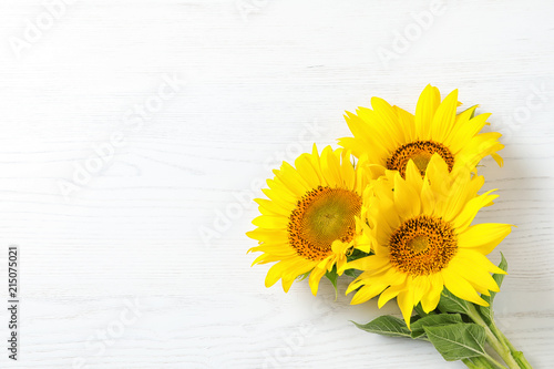 Yellow sunflowers on wooden background, top view