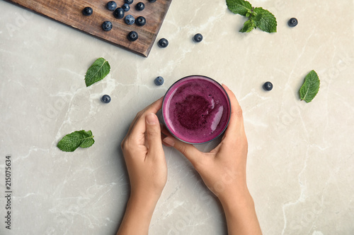 Woman holding glass of delicious acai juice on table, top view