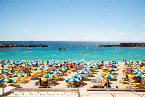 Photo  Las Americas, Canarias islands/ Spain-July 22, 2018: View of beach fool of tourists and umbrellas for sun on Canarias, view of bay with mountains