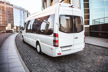 White mini bus moves down the street