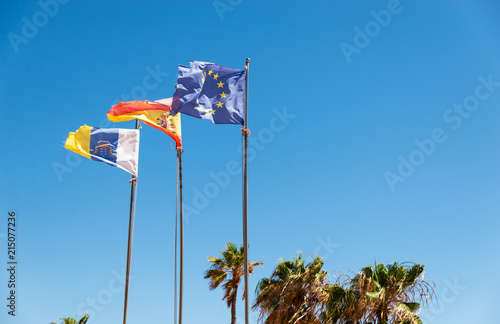 Foto op Aluminium Canarische Eilanden Canarias islands/ Spain-July 22, 2018: View from distance of tree flags of Spain, Europe Union and Canarias islands on blue sky and palms leaves background.