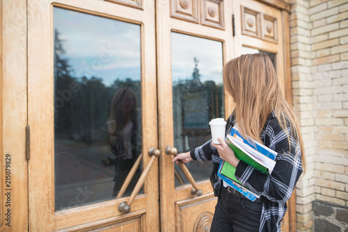 Photo  A girl student in casual clothing, books and notebooks in his hands opens the door to the university