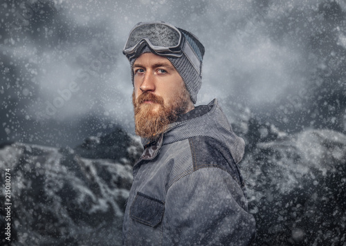 Fotografiet  Portrait of a redhead snowboarder with a full beard in a winter hat and protective glasses dressed in a snowboarding coat posing at a studio, looking away