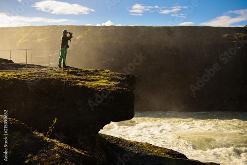 Photo Cascada de Gullfoss con senderista observando con prismáticos, Islandia