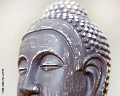 Tuinposter Boeddha Buddha's face close-up. The Buddha image in ceramics. The texture of the background and focus of the soft focus.