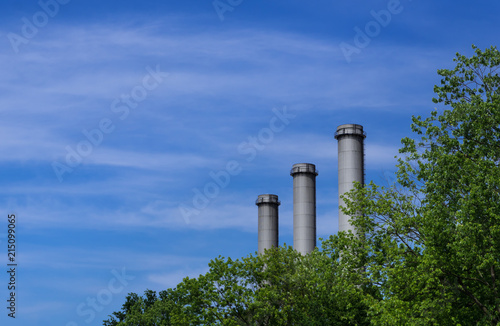 Leinwand Poster Modern Smokestacks behind Trees Blue Sky Berlin Germany