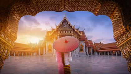 Žena s crvenim kišobranom na ulazu u mramorni hram u Bangkoku