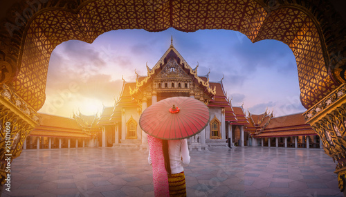 Woman holding traditional red umbrella on the Marble Temple, Wat Benchamabopitr Dusitvanaram at sunrise in Bangkok, Thailand.