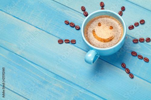Kaffee Tasse mit lächelndem Gesicht Emoji Smiley auf blauem Holz Tisch
