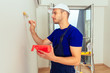 Worker in blue uniform is painting wall in the white. Home renovation concept.