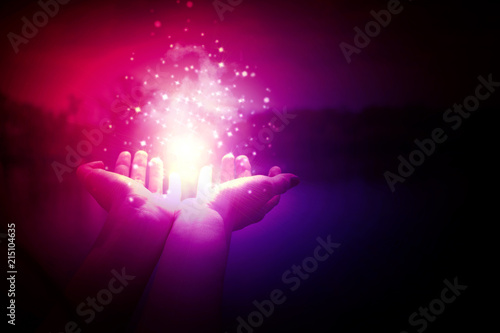 Photo  Magic particles on the palms of a woman on a dark, purple background
