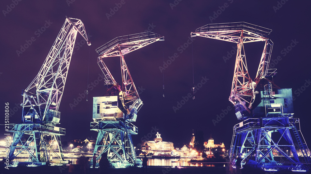 Fototapeta Illuminated old port cranes on a boulevard in Szczecin City at night, color toning applied, Poland.