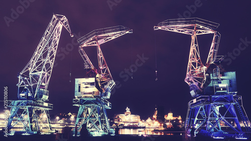 Obraz Illuminated old port cranes on a boulevard in Szczecin City at night, color toning applied, Poland. - fototapety do salonu