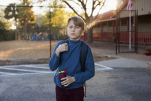 A Boy Standing Outside Of His School