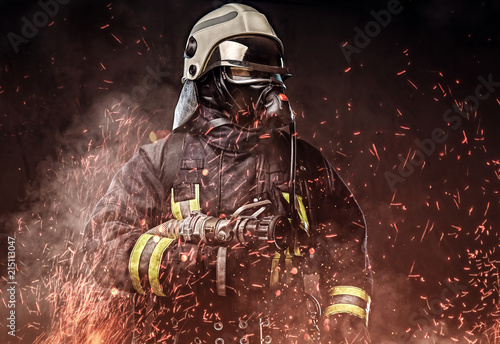 A firefighter dressed in a uniform in a studio. Lerretsbilde