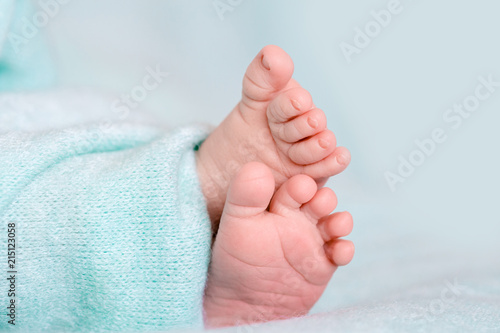 Foto  Small and soft legs of a newborn baby in a blue blanket