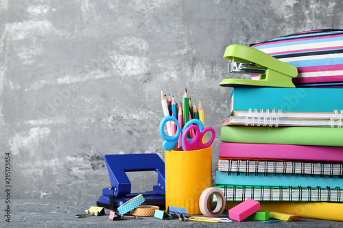 School supplies with books and notebooks on grey background - 215123654