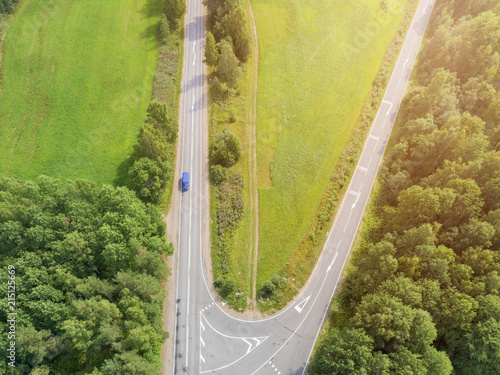 Fototapeta Aerial view of highway with car. Aerial view of a country road with moving car. Car passing by. Aerial road. Aerial view flying. Captured from above with a drone. Soft lighting obraz na płótnie