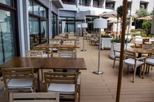 Empty Resort Hotel Yard Patio Cafe With Wooden White Furniture Chairs Armchairs Tables And Umbrellas