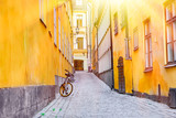 Fototapeta Uliczki - The narrow cobblestone street with a bicycle and yellow medieval houses of Gamla Stan historic old center of Stockholm at summer sunny day.