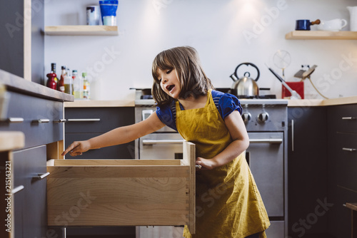 Girl looking in kitchen drawer
