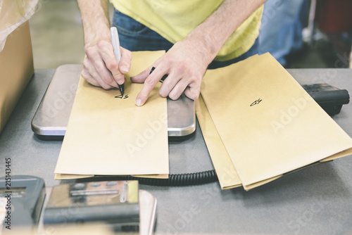 Worker Writing On Paper bags At Table In Coffee Industry