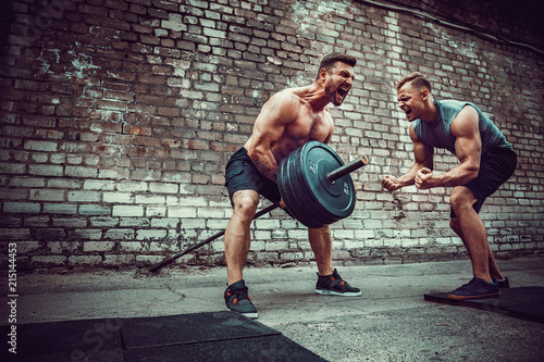 Two muscular athletes training, one raise the bar when other is motivating Canvas-taulu