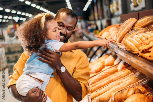 Fotografía african american little child pointing by finger at pastry to father in supermar