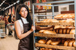 young african american female shop assistant in apron arranging fresh pastry in supermarket