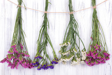 Dried Flowers Limonium Multicolored, Tied With A Jute Rope, Hang On A White Wooden Wall Or Fence