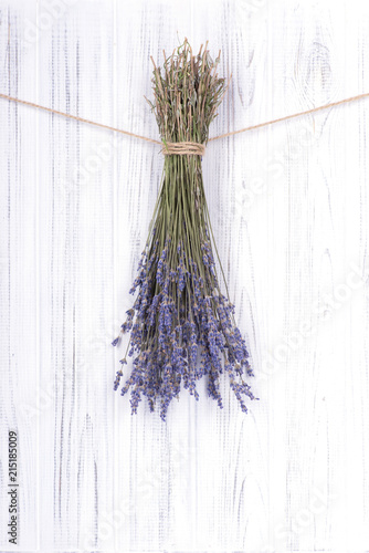 Poster Graffiti Dried flowers lavander, tied with a jute rope, hang on a white wooden wall or fence