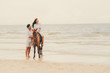 Young couple goes horse riding on tropical beach.