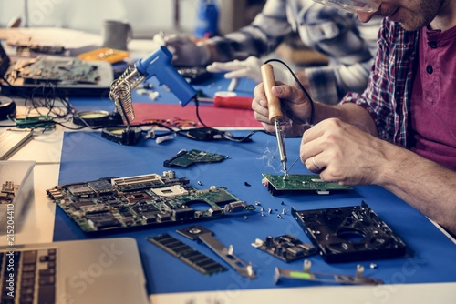 Fotomural  Hand soldering tin on electronics circuit board