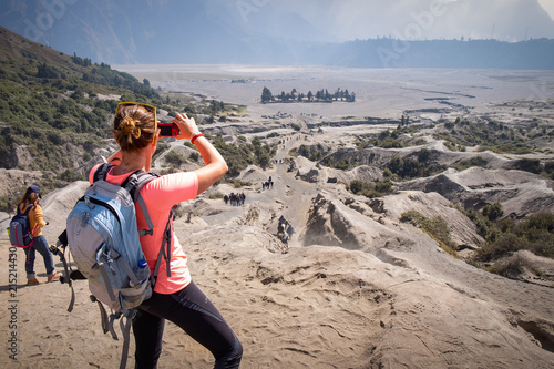 East Java, Indonesia - July 18, 2018 : Woman trekker taking photos of beautiful landscape and tourist ride a horse and walking on the volcano desert at Mount Bromo in Indonesia, by mobile phone.