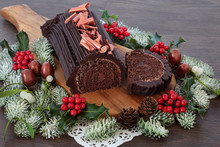 Chocolate Yule Log Christmas Cake With Winter Flora Of Snow Covered Fir, Holly, Acorns And Mistletoe On Rustic Oak Wood Background. Festive Food  For The Holiday Season.