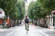 Man Riding Bike On Road In Town