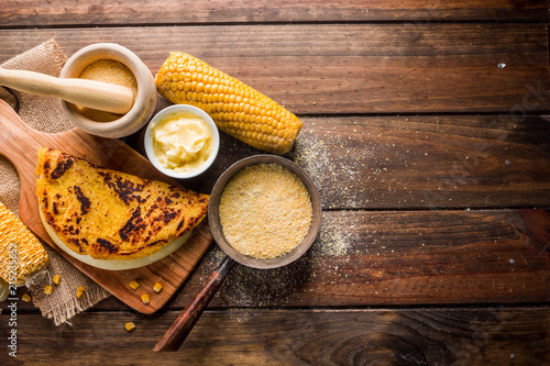 Typical Venezuelan cuisine, Top view of a wooden table with several ingredients for the preparation of Cachapas with cheese, corn, butter, ground corn and white cheese